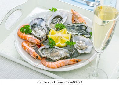 Champagne glass, oysters shell with shrimp on serving tray, top view