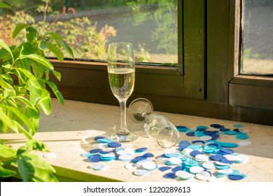 A champagne glass with champagne and a second glass lying on the windowsill with blue confetti