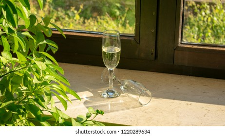 A champagne glass with champagne and a second glass lying on the windowsill in the sunshine