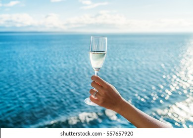 Champagne glass woman's hand toasting on ocean background at luxury cruise ship during sunset. Travel vacation for honeymoon, lady holding flute wearing wedding ring.