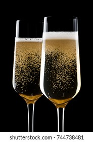 Champagne glasses with bubbles with reflection on black background