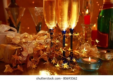 Champagne in glasses ,candle lights,gift boxes and light on background.