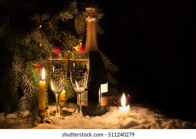 Champagne glasses and candles in Christmas eve