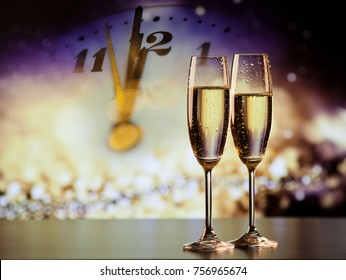 champagne glasses and clock at twelve against holiday lights - new year's eve