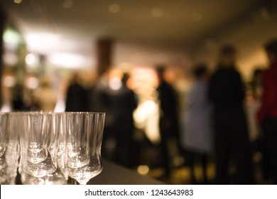 Champagne glasses at a dinner party, with party guests in background out of focus