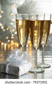 Champagne in glasses, gift box and lights on silver background.