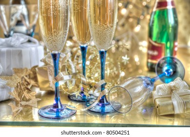 Champagne in glasses, gift boxes and lights on background.