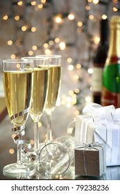 Champagne in glasses, gifts and blurred lights on background.