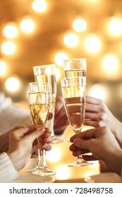 Champagne glasses in hands on golden background. Party and celebration concept
