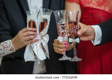 Champagne glasses held by married young people