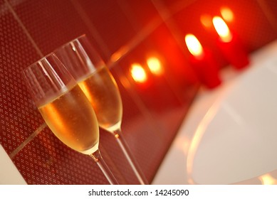 Champagne glasses on the edge of a candle-lit bath