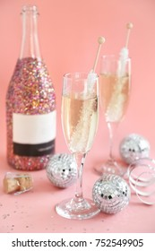 Champagne glasses on pink background with glitter wine bottle