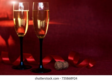 Champagne glasses on sparkling holiday background. Fireworks at New Year party and holiday celebration concept. Photo of two champagne glasses against background with sparkles.