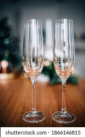 Champagne glasses on the table against the background of the Christmas tree