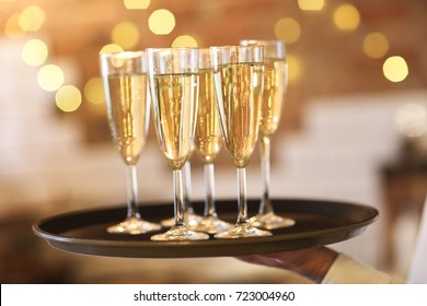 Champagne glasses on tray in bright lights. Party or celebration