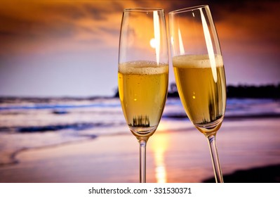 Champagne glasses on tropical beach at sunset - exotic New Year