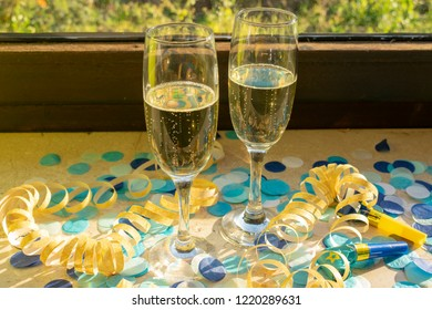 Champagne glasses on the windowsill with confetti and streamers