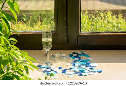 Champagne glasses on the windowsill in sunlight with blue confetti