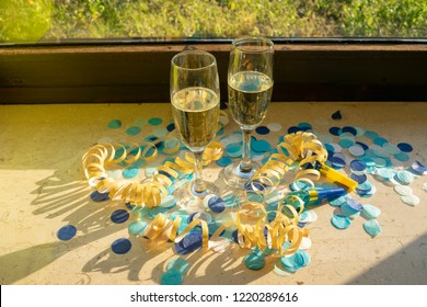 Champagne glasses with champagne on the windowsill in the sunshine with confetti and streamers
