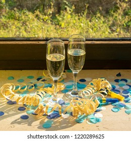 Champagne glasses with champagne on the windowsill in the sunshine with blue confetti and yellow streamers