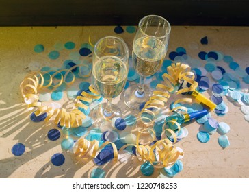 Champagne glasses with champagne on the windowsill in the sunshine with blue confetti, yellow streamers and rolling pipes