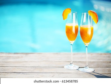 Champagne glasses with peach. Bellini cocktail. Summer pool party