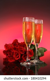 champagne glasses with red roses on pink background