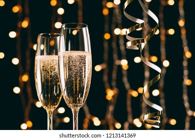 champagne in glasses and ribbons on garland light background, christmas concept