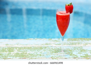 Champagne glasses with strawberry on turquoise background. Rossini cocktail. Summer pool party