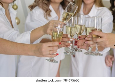 champagne in the hands of girls in white shirts. New Year's greetings