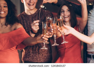 Champagne is an integral part. Multiracial friends celebrate new year and holding bengal lights and glasses with drink.