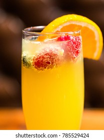 Champagne mimosa with fruit and orange in glass