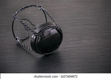 Champagne muselet with black cap on black stone background. Close-up