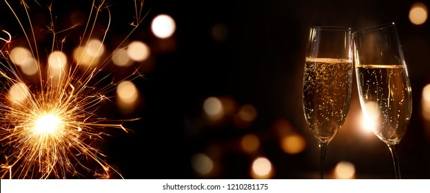 Champagne for the new year on dark background with sparkler and festive golden bokeh