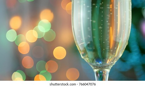Champagne pour with Christmas lights into glass. Pouring wine bubbles and foaming over holiday bokeh blinking background. Success Christmas celebrating