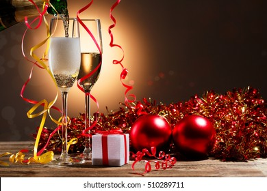 Champagne pouring from bottle into glasses and Christmas decorations
