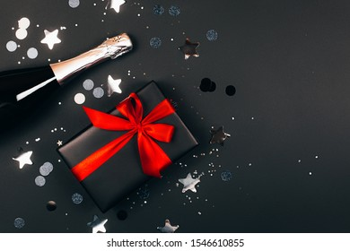 Champagne with present box on dark background. Festive concept. Flat lay style. Black box with red bow.