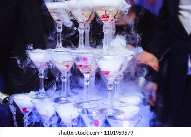 Champagne slide. Pyramid or fountain made of champagne glasses with cherry and steam from dry ice. Wedding party catering wine glasses. Event planner concept