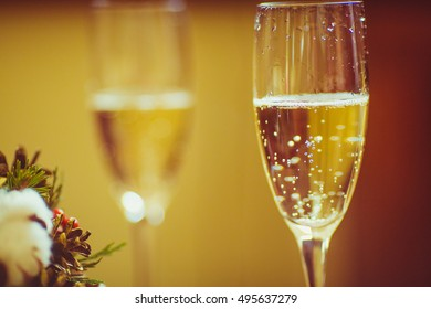 Champagne sparkles in the glasses on the beig background