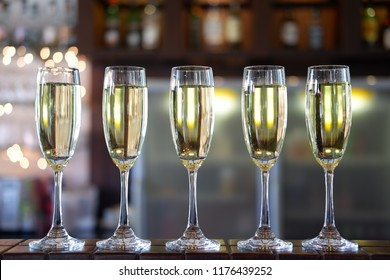 champagne and sparkling wine glass at bar and night time party, bar background