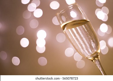 Champagne sparkling wine glass in disco party at night with defocused festive Christmas and New Year lights in nightclub.