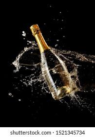 Champagne splash over a full golden bottle
