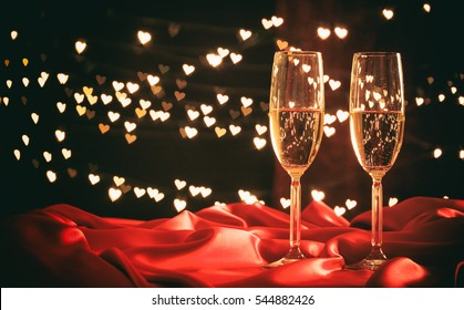 Champagne for valentines.Two champagne glasses on hearts bokeh background