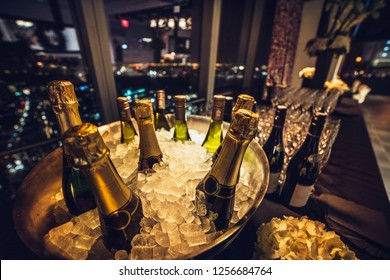 Champagne wine bottles on ice on catering table on luxury city eventt