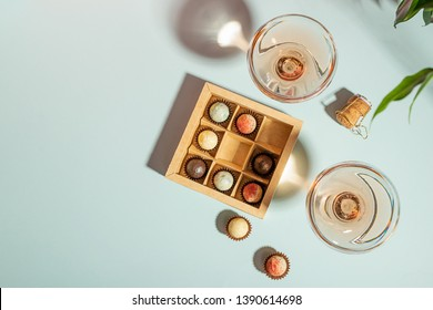 Champagne or wine in elegant glasses, a box of chocolates on a blue background. Copy space. Flat layout top view.