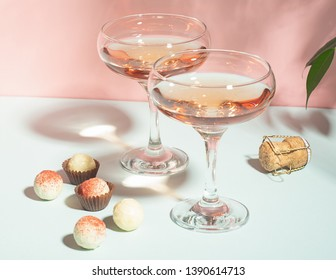 Champagne or wine in elegant glasses various chocolates of white chocolate on a pink background hard light. Copy space.