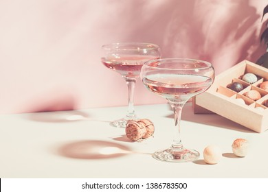 Champagne or wine in glasses box of chocolates of white and dark chocolate on pink background bright light. Copy space.