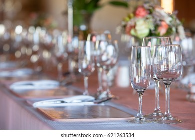 Champagne and wine glasses on table decorated with flowers at wedding reception. Selective focus on glasses.