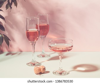 Champagne or wine in various elegant glasses on a pink background bright light. Copy space. S Horizontal frame. Toning