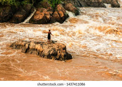 Champasak, Laos - OCTOBER 24, 2010: Laotian fisherman stands on the rapid while casting fishing net on the Mekong River. Li Phi Waterfall.